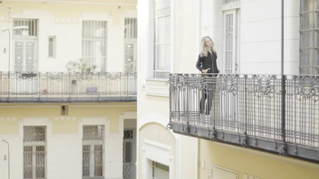 beautiful woman posing on a balcony - balcony stock videos and b-roll footage