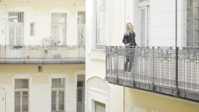 stockvideo's en b-roll-footage met mooie vrouw poseren op een balkon - balkon