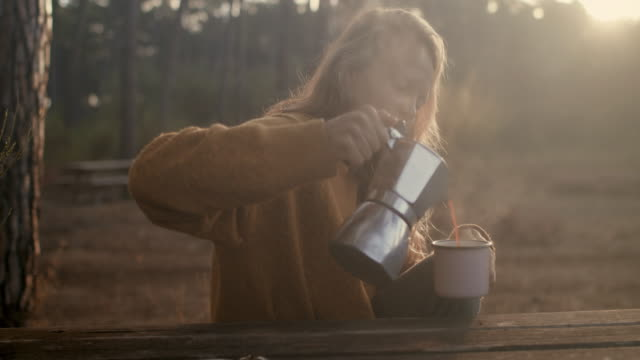 Beautiful woman pouring fresh coffee at picnic table in the forest in the morning at sunrise in the South of France.
