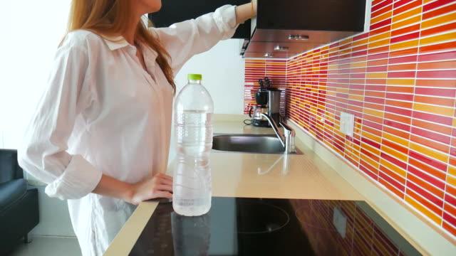 Mooie vrouw gieten van water in een glas