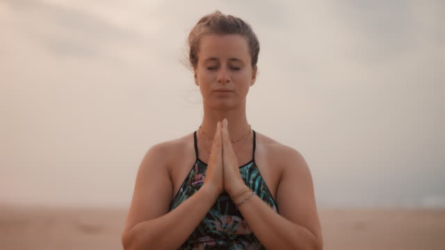 beautiful woman practicing yoga/meditating on the beach at sunset in france - zen like stock videos & royalty-free footage