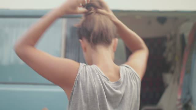 Beautiful woman putting hair up in front of van/camping in the morning