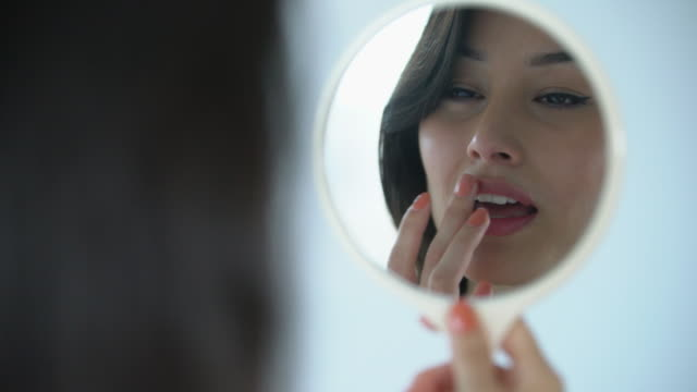 cu beautiful woman putting on makeup in a mirror. - specchio video stock e b–roll
