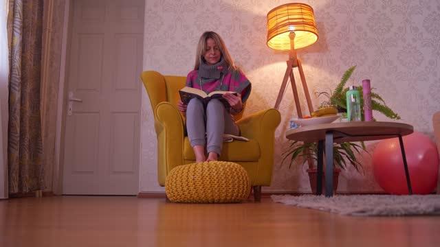 vídeos de stock e filmes b-roll de beautiful woman reading book in comfort of her living room - electric lamp