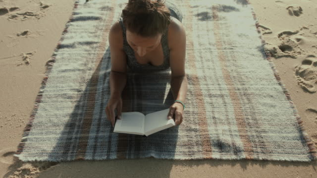 beautiful woman reading book on a blanket at the beach at the atlantic ocean in the south of france - grau stock-videos und b-roll-filmmaterial