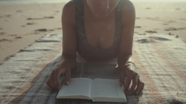 stockvideo's en b-roll-footage met beautiful woman reading book on a blanket at the beach at the atlantic ocean in the south of france - literature