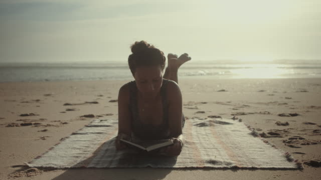Beautiful woman reading book on a blanket at the beach at the Atlantic ocean in the south of France