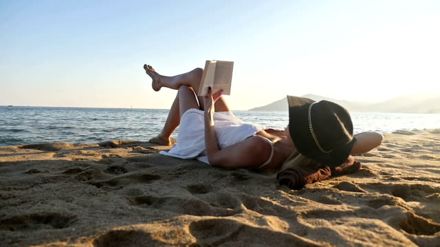 beautiful woman reading on beach - reclining stock videos & royalty-free footage