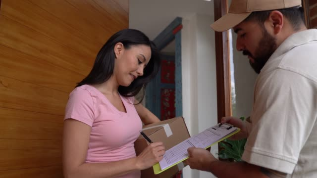 beautiful woman receiving a box from postal worker and signing off a sheet smiling - receiving stock videos & royalty-free footage