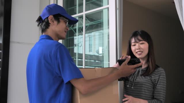 vidéos et rushes de belle femme recevant et signant un colis du facteur livré dans sa maison - 10 seconds or greater