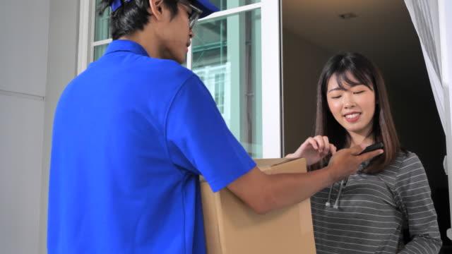 vídeos de stock, filmes e b-roll de mulher bonita recebendo e assinando um pacote de carteiro entregue em sua casa - 10 seconds or greater