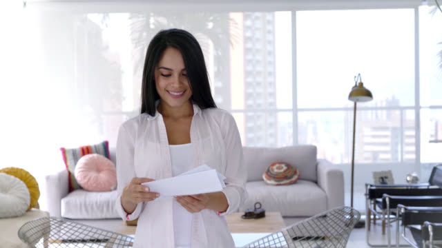 Beautiful woman receiving correspondence at home