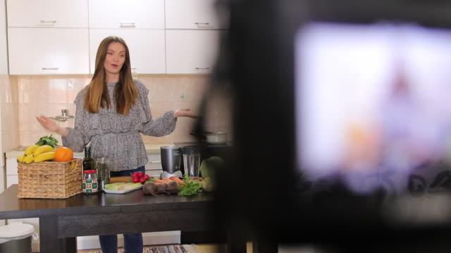vidéos et rushes de beau blog vidéo d'enregistrement de femme au sujet de la nourriture saine à la maison - influenceur