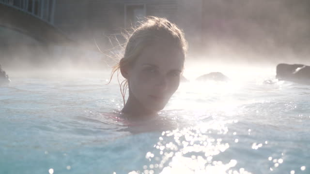 beautiful woman relaxing in hot spring pool in iceland - spa stock videos & royalty-free footage