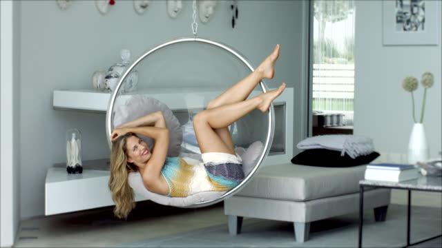 vidéos et rushes de beautiful woman relaxing in swing chair - jambe