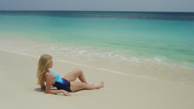 beautiful woman relaxing on ocean beach / grand anse beach, grenada - ausgefranst stock-videos und b-roll-filmmaterial