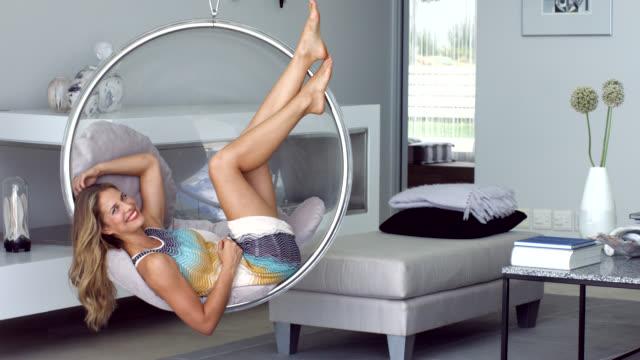beautiful woman relaxing on swing chair - gelassene person stock-videos und b-roll-filmmaterial