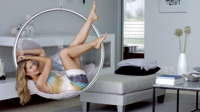 beautiful woman relaxing on swing chair - behaglich stock-videos und b-roll-filmmaterial