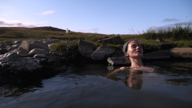 beautiful woman resting in hot natural pool in iceland - taking a bath stock videos & royalty-free footage