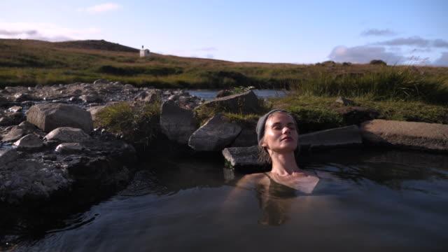 schöne frau ruht in heißen natürlichen pool in island - ein bad nehmen stock-videos und b-roll-filmmaterial