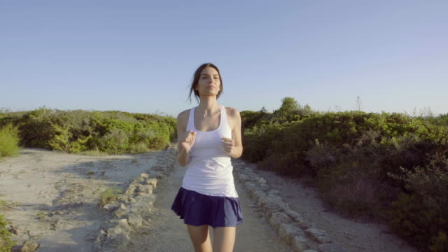 beautiful woman running in the afternoon - silvestre stock-videos und b-roll-filmmaterial