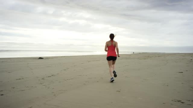 vídeos y material grabado en eventos de stock de hermosa mujer corriendo en la playa - noroeste pacífico de los estados unidos