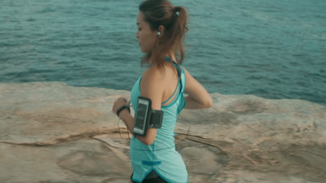 beautiful woman runs near the ocean (slow motion) - headphones stock videos & royalty-free footage