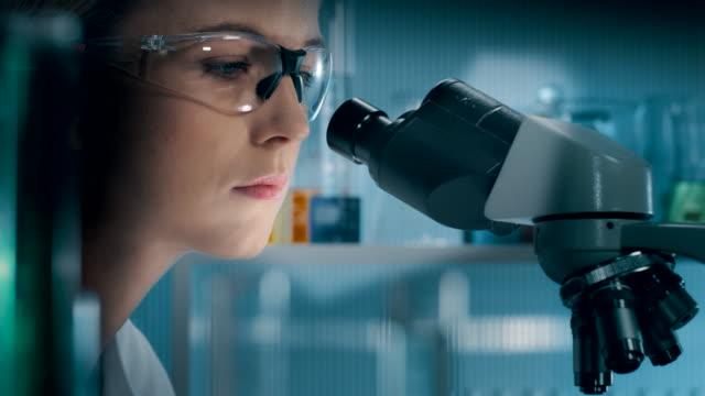 vidéos et rushes de belle étudiante femme scientifique médecin examinant l'échantillon dans le tube à essai - curiosité