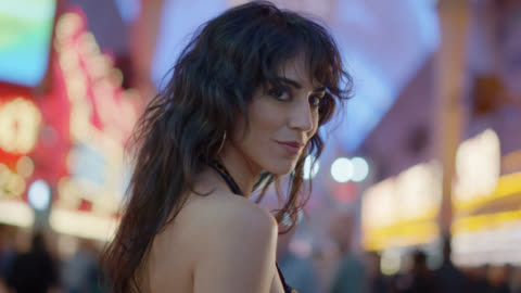 slo mo. beautiful woman seductively flirts with camera walking down fremont st. in las vegas - looking away video stock e b–roll