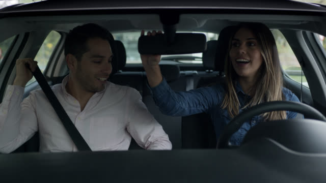 vidéos et rushes de belle femme fixant les miroirs de voiture prêt pour un essai routier - conducteur métier