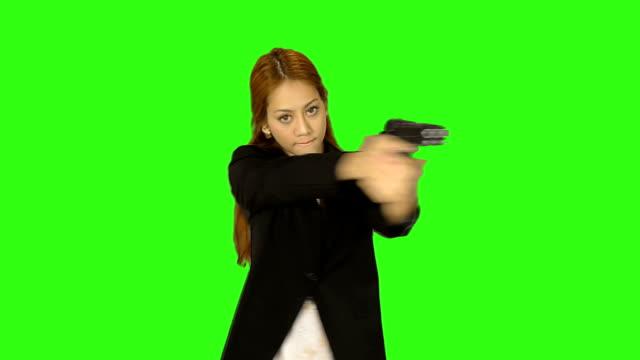 schöne frau fotografieren gun mit green-screen-hintergrund - sportschießen stock-videos und b-roll-filmmaterial