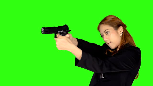 stockvideo's en b-roll-footage met beautiful woman shooting gun with green screen background - keyable