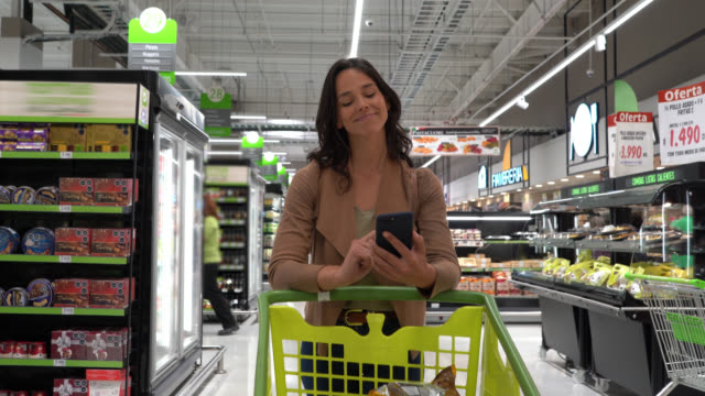 beautiful woman shopping for groceries at the supermarket looking at a list on smartphone - cart stock videos & royalty-free footage