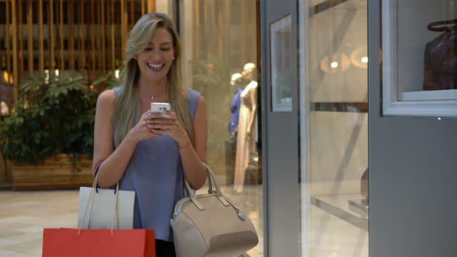 vídeos de stock e filmes b-roll de beautiful woman shopping in the mall while texting and looking at retail displays - mercadoria