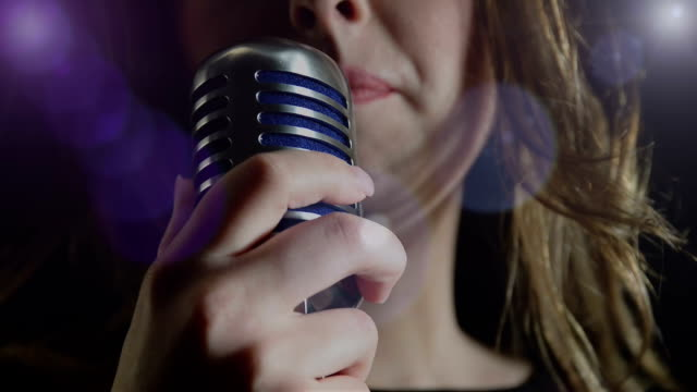 beautiful woman singing to the microphone in a studio - microphone stock videos & royalty-free footage
