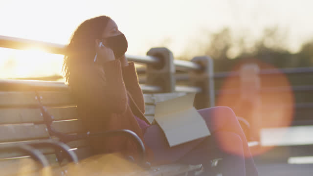 beautiful woman sits outdoors on bench and removes her protective face mask - diary stock videos & royalty-free footage