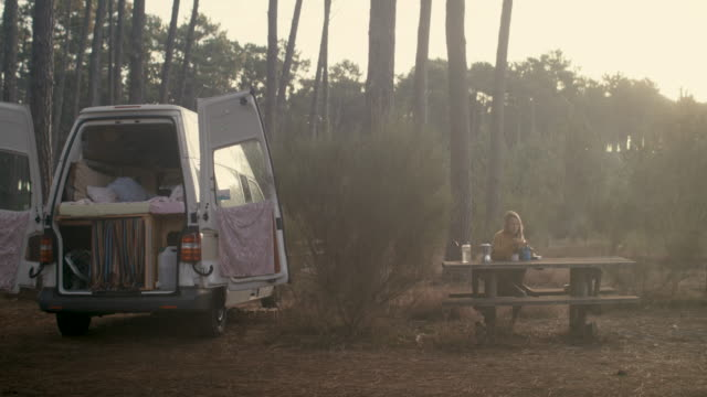 Beautiful woman sitting at picnic table next to motor home in the pine forest at sunrise making coffee on camping stove in the South of France.