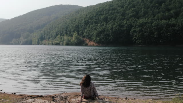 beautiful woman sitting by the lake - island stock videos and b-roll footage