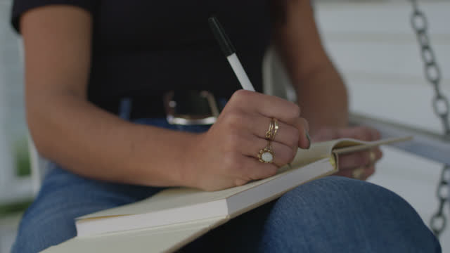 slo mo cu beautiful woman sitting on porch swing looks down at journal, begins to write - diary stock videos & royalty-free footage