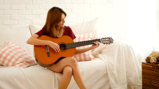beautiful woman sitting on sofa in living room at home and playing acoustic guitar - chitarra video stock e b–roll