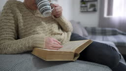 Beautiful woman sitting on the bed and reading a book at home