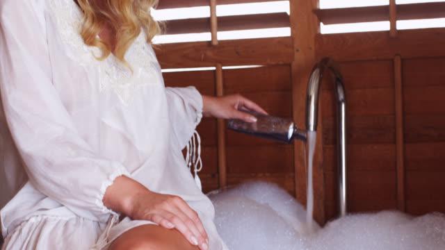 vidéos et rushes de beautiful woman sitting on the edge of a bath and pouring bath foam from a bottle. - beaux pieds et femme