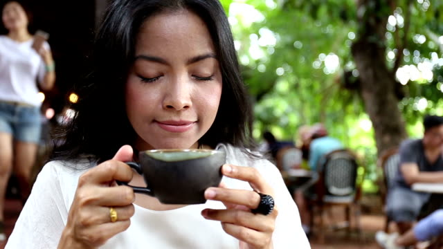 Beautiful woman smelling the aroma of her morning coffee in garden