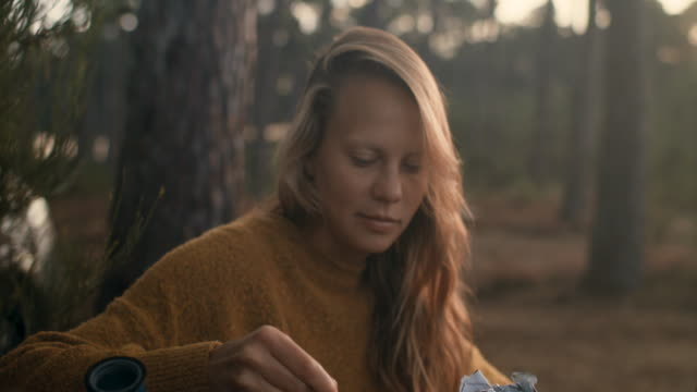 beautiful woman smiling, making coffee in espresso machine on camping table in the morning in the forest in france. - kamerawinkel stock-videos und b-roll-filmmaterial