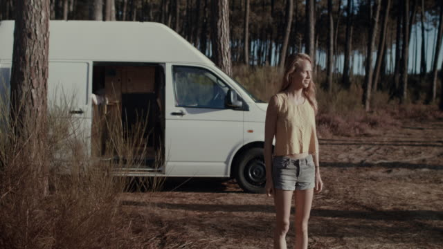 beautiful woman smiling standing in the forest in the south of france by her van/motorhome in the morning at sunrise. - generation z stock-videos und b-roll-filmmaterial
