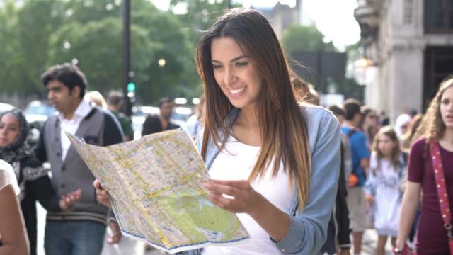 vídeos de stock, filmes e b-roll de mulher bonita em pé sobre uma rua ocupada olhando para um mapa - turista