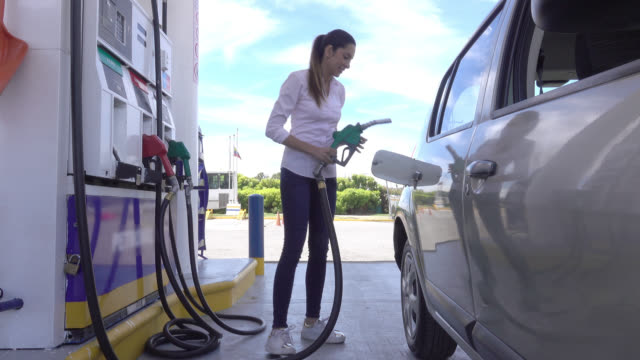 beautiful woman stopping at gas station to refuel her car - refuelling stock videos & royalty-free footage