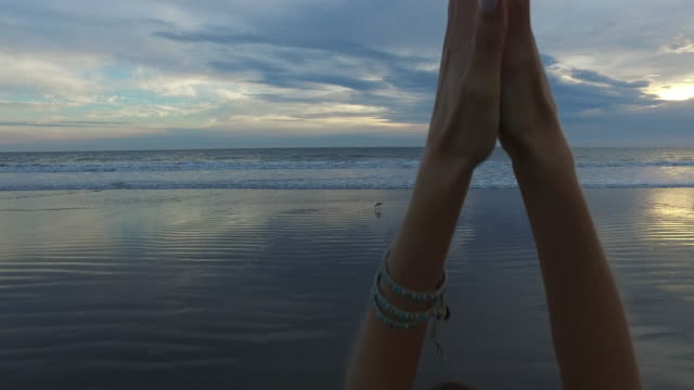 A beautiful woman stretching her arms out while standing on the beach in Santa Monica, California, USA at sunset, 4K