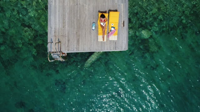 beautiful woman sunbathing alone on a wooden pier in sea aerial 4k video - mugla province stock videos & royalty-free footage