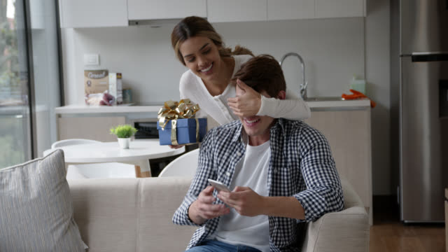 beautiful woman surprising her partner with a gift while he is texting on smartphone relaxing on couch - anniversary stock videos & royalty-free footage